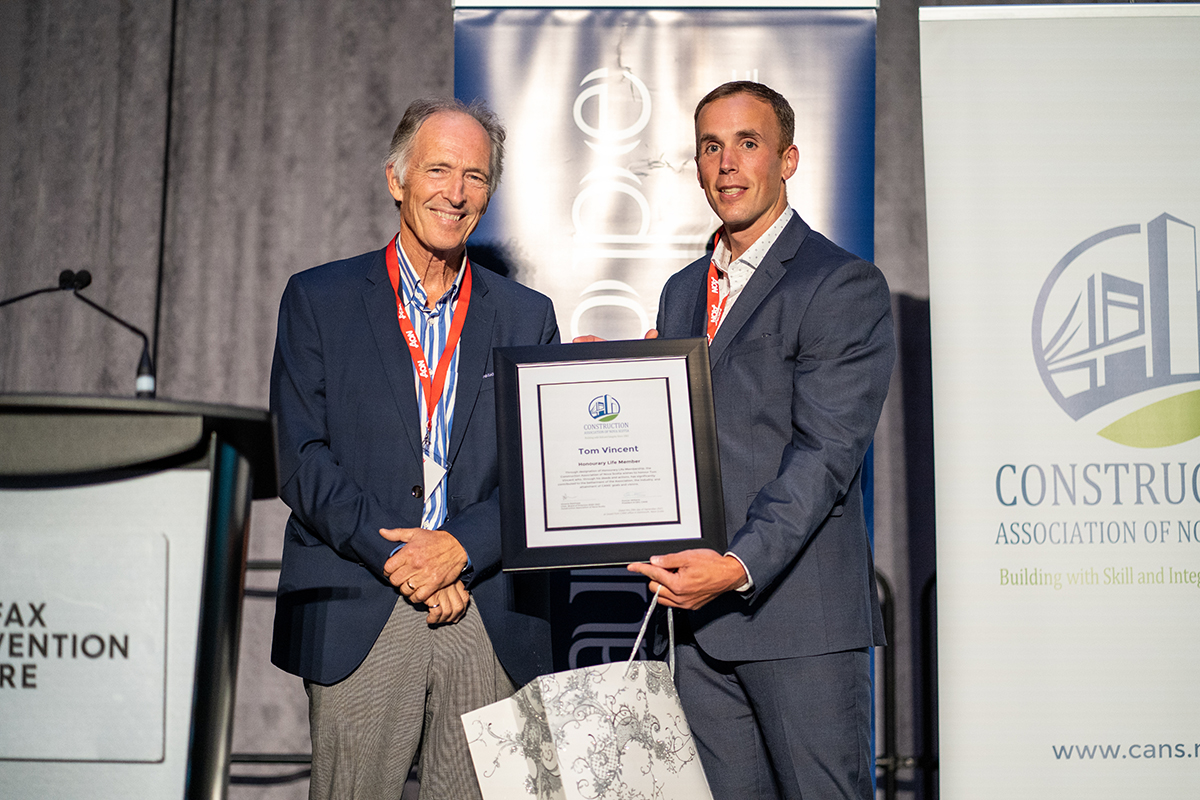 Two men stand on stage, one is handing the other a certificate and gift in recognition of him being honoured with CANS Honourary Life Member award.